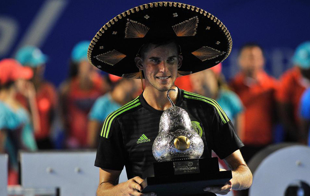 Austria´s tennis player Dominic Thiem wears a traditional Mexican mariachi hat while holding the winning trophy after defeating Australia's Bernard Tomic during their Mexico ATP 500 Open men's single tennis final in Acapulco, Guerrero state, Mexico on February 27, 2016. / AFP / PEDRO PARDO AND Pedro Pardo